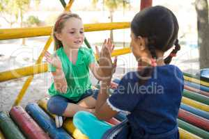 Girls playing clapping game while sitting on jungle gym
