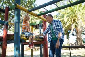 Happy father talking to son sitting on jungle gym