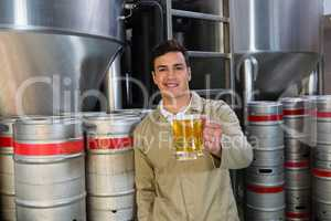 Portrait of smiling man holding beer glass against storage tanks