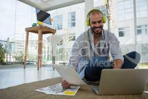 Smiling desginer holding collage using laptop at workshop