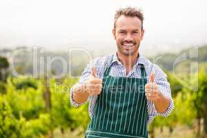 Portrait of smiling young man showing thumbs up sign