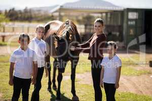 Happy family standing with a brown horse in the ranch