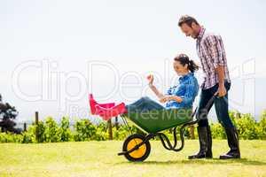 Young man pushing woman sitting in wheelbarrow