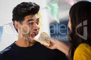 Woman feeding tortilla to friend