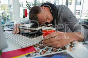 Businessman holding cup sleeping on files at desk