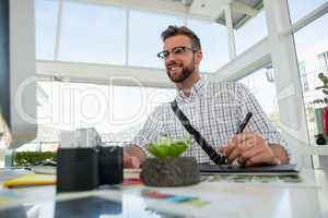 Graphic designer writing on tablet while sitting at desk