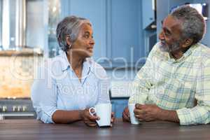 Couple talking while having coffee in kitchen