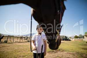Smiling girl holding the rein of the horse in the ranch