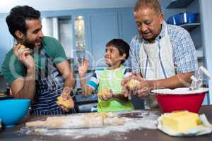 Playful family holding dough while preparing food