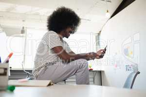 Man using phone while sitting on desk at office