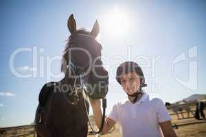 Rider girl standing with a horse in the ranch