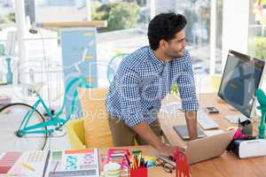 Graphic designer working on laptop at desk
