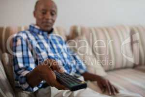 Man holding remote control while sitting on sofa