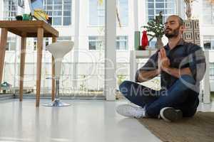 Businessman in prayer position meditating at studio