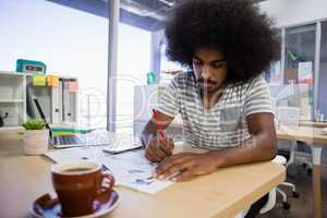 Concentrated man writing on document at office