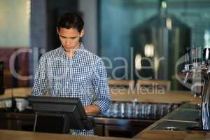 Bar tender operating cash desk at counter