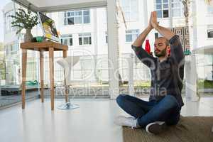 Designer in prayer position meditating while sitting on floor