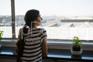Rear view of woman looking through window at office