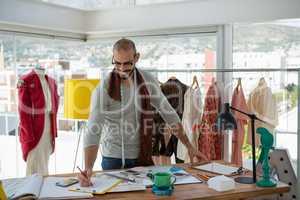 Designer drawing sketch at table in workshop