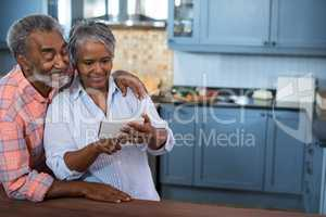 Couple using mobile phone in kitchen