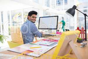 Graphic designer working on computer at desk