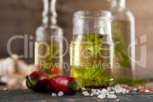 Close up of jalapeno pepper by spices and herbs with oil in containers