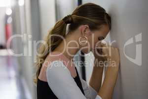 Frustrated businesswoman leaning on wall