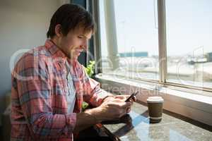 Businessman using phone while sitting by window