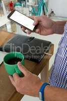 Designer using mobile phone while holding drink at table