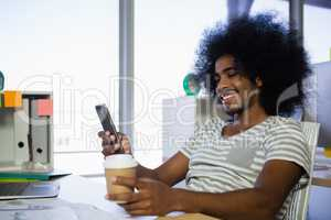 Smiling man using phone while having coffee in office