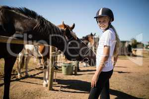 Smiling girl standing near the horse in ranch