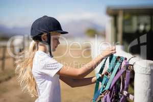 Girl picking up a horse muzzle in the ranch