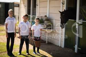 Kids standing with a bucket to feed the horse