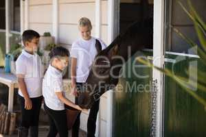 Three kids feeding the horse in stable