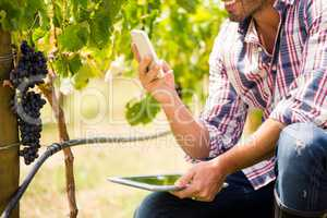 Midsection of man using phone while holding tablet