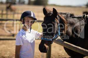 Smiling girl standing near the brown horse in the ranch