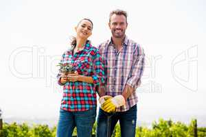Portrait of smiling woman with man holding potted plant