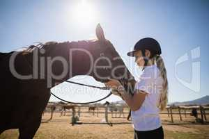 Rider girl caressing a horse in the ranch