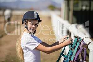 Smiling girl picking up a horse muzzle in the ranch