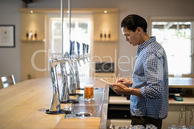 Bar tender using digital tablet at counter