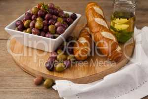 High angle view of olives in container by bread and oil