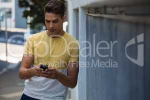 Confident young man using mobile phone