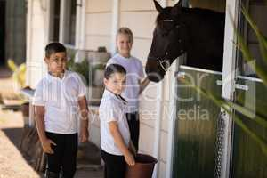 Smiling kids feeding the horse in stable