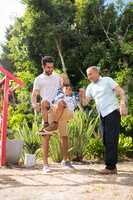 Playful father and grandfather with boy at park