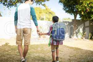 Rear view of father holding hand of son with backpack in yard