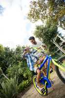 Tilt image of father assisting son for riding bicycle