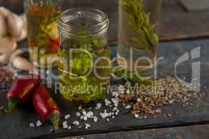 Jalapeno pepper by spices and herbs with oil in containers