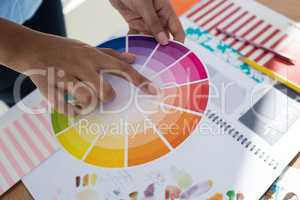 Graphic designer holding color swatch at desk