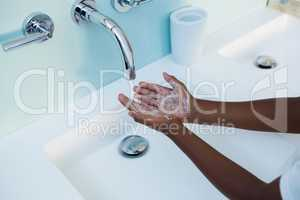High angle view of boy washing hands in sink