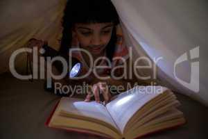 Girl holding flashlight while reading novel under blanket